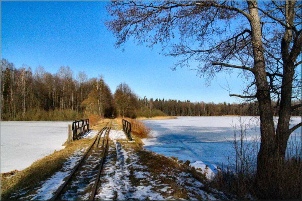 Zu sehen ist ein See mit Bahngleisen in Hajnowka, Bild: Franczesko-Genelli